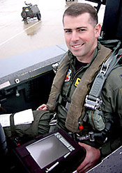 A U.S. Air Force weapon systems officer displays the tablet PC used aboard an F-15 strike fighter.